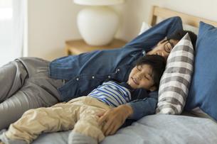 ベッドで眠る父親と息子の写真素材 [FYI01733537]