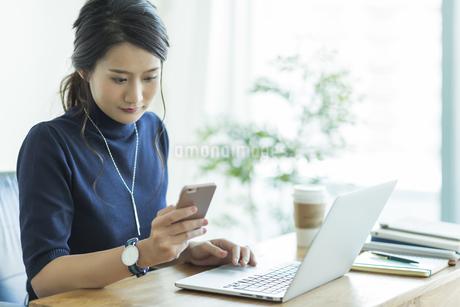 スマートフォンを操作するビジネスウーマンの写真素材 [FYI01733542]