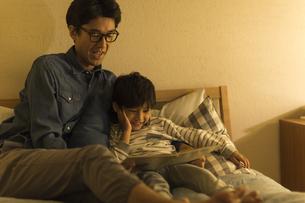 ベッドで絵本を読む父親と息子の写真素材 [FYI01733560]