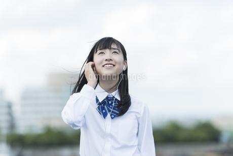 イヤホンで音楽を聴く女子学生の写真素材 [FYI01733564]