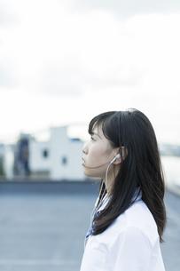 イヤホンで音楽を聴く女子学生の写真素材 [FYI01733582]