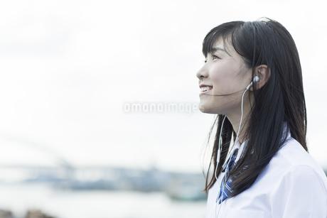 イヤホンで音楽を聴く女子学生の写真素材 [FYI01733594]