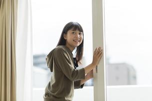 窓辺で振り返る女の子の写真素材 [FYI01733602]