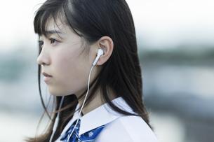 イヤホンで音楽を聴く女子学生の写真素材 [FYI01733663]