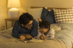 ベッドで絵本を読む父親と息子の写真素材 [FYI01733671]