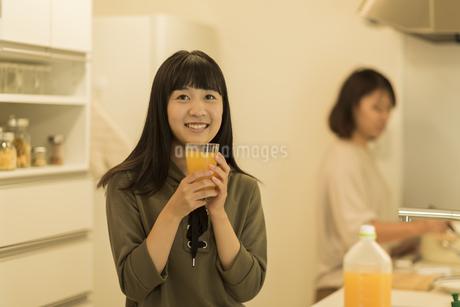 キッチンでコップに入ったジュースを飲む女の子の写真素材 [FYI01733673]