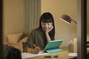 タブレットPCで勉強をする女の子の写真素材 [FYI01733677]