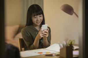 スマートフォンを見ながら勉強をする女の子の写真素材 [FYI01733680]