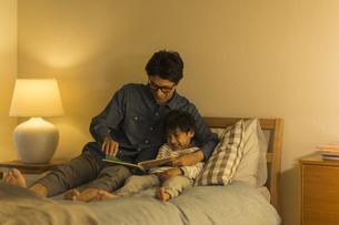 ベッドで絵本を読む父親と息子の写真素材 [FYI01733684]