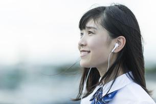 イヤホンで音楽を聴く女子学生の写真素材 [FYI01733686]