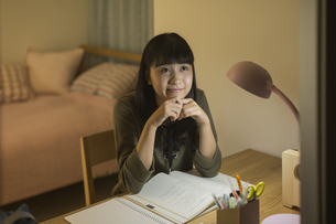 机で勉強をする女の子の写真素材 [FYI01733691]