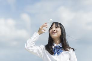ペットボトルを頭にあてる女子学生の写真素材 [FYI01733705]