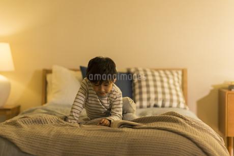 ベッドで本を読む男の子の写真素材 [FYI01733708]