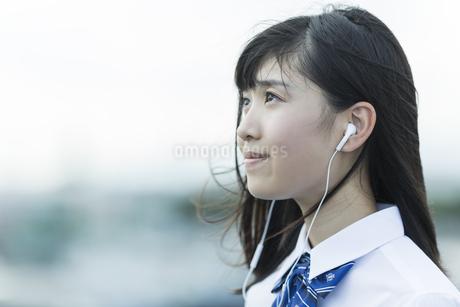 イヤホンで音楽を聴く女子学生の写真素材 [FYI01733724]