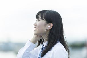 イヤホンで音楽を聴く女子学生の写真素材 [FYI01733748]