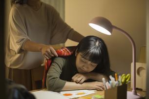 机で居眠りをする女の子の写真素材 [FYI01733750]
