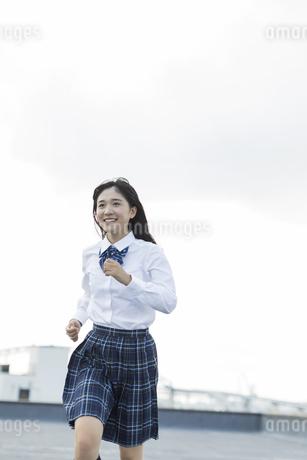 屋上で走る女子学生の写真素材 [FYI01733769]