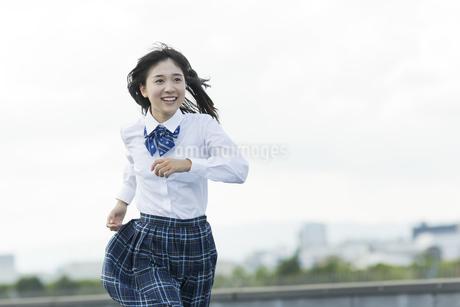 屋上で走る女子学生の写真素材 [FYI01733770]