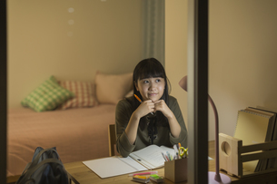 机で勉強をする女の子の写真素材 [FYI01733779]