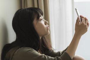 スマートフォンを見る女の子の写真素材 [FYI01733810]