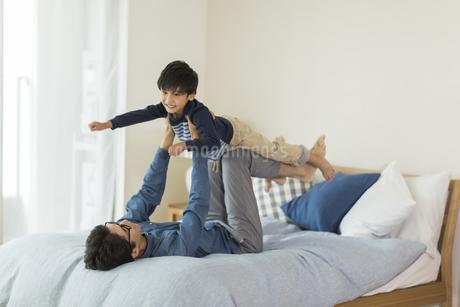 ベッドの上で遊ぶ父親と息子の写真素材 [FYI01733811]