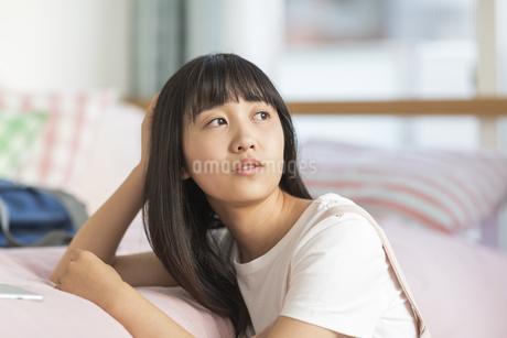 ベッドにもたれる女の子の写真素材 [FYI01733839]