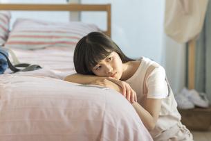 ベッドにもたれる女の子の写真素材 [FYI01733878]