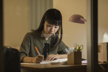机で勉強をする女の子の写真素材 [FYI01733891]