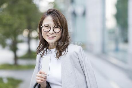 スマートフォンを持ち笑顔のビジネスウーマンの写真素材 [FYI01733904]