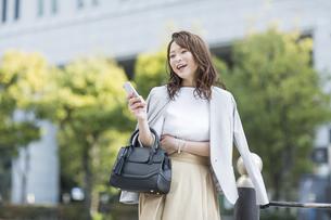 スマートフォンを持ち笑顔のビジネスウーマンの写真素材 [FYI01733924]