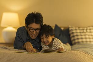 ベッドで絵本を読む父親と息子の写真素材 [FYI01733937]