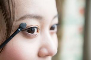 アイシャドウを塗る30代女性の目元の写真素材 [FYI01733997]