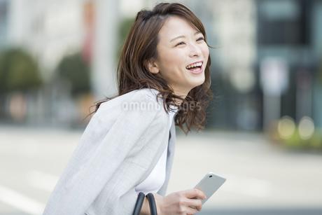スマートフォンを持ち笑顔のビジネスウーマンの写真素材 [FYI01734027]