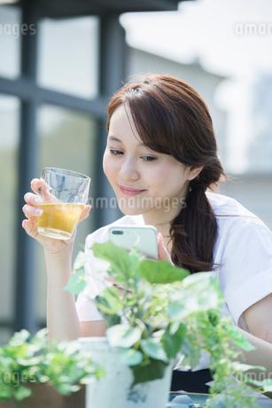 屋外でドリンクを持ちスマホを操作する30代女性の写真素材 [FYI01734063]