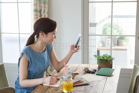 スマホを持ち笑顔でメモを取る30代女性の写真素材 [FYI01734121]