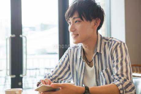 スマホを持ち会話をする笑顔の20代男性の写真素材 [FYI01734133]