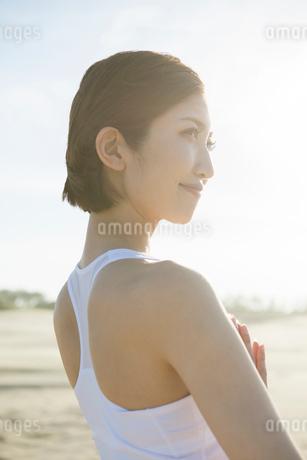 浜辺でヨガをする20代女性の写真素材 [FYI01734136]