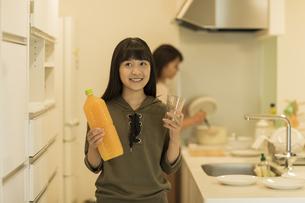 キッチンでジュースとコップを持つ女の子の写真素材 [FYI01734171]