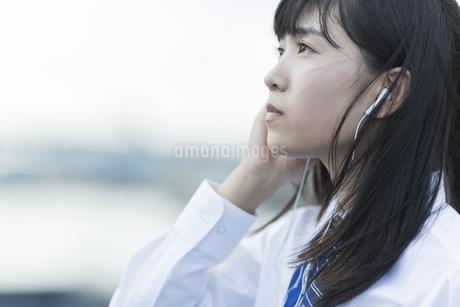 イヤホンで音楽を聴く女子学生の写真素材 [FYI01734181]