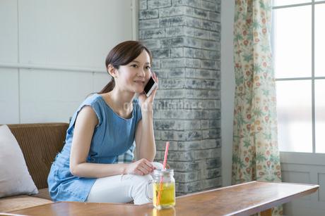 部屋で通話をする30代女性の写真素材 [FYI01734201]