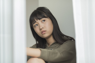 窓辺に座る女の子の写真素材 [FYI01734207]