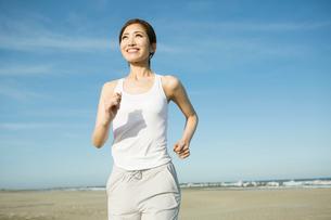 浜辺でランニングをする20代女性の写真素材 [FYI01734225]