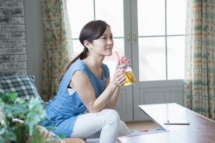 部屋で飲み物を飲む30代女性の写真素材 [FYI01734258]