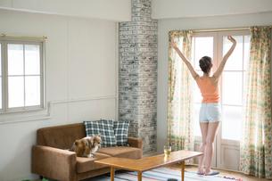 部屋のカーテンを開けストレッチをする女性の写真素材 [FYI01734264]