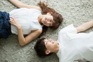 寝転がり見つめ合う笑顔の20代男女の写真素材 [FYI01734272]