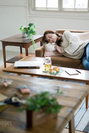 ソファでうたた寝をする30代女性の写真素材 [FYI01734291]