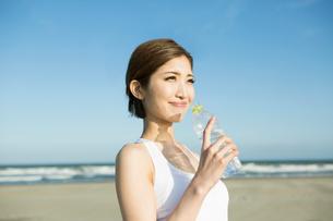 浜辺で水を飲む20代女性の写真素材 [FYI01734341]