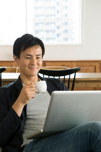 ソファに座りパソコンを操作する笑顔の30代男性の写真素材 [FYI01734354]