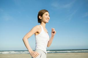 浜辺でランニングをする20代女性の写真素材 [FYI01734367]