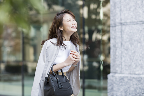 スマートフォンを持ち笑顔のビジネスウーマンの写真素材 [FYI01734383]